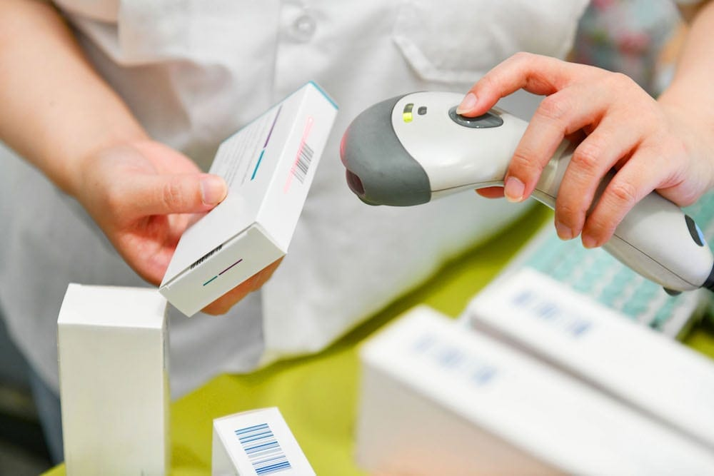 Pharmacist scanning barcode of medicine drug